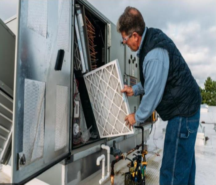 man replacing filter in commercial hvac system