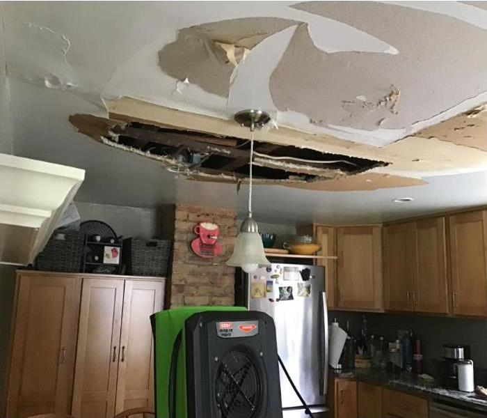 green drying equipment in kitchen with missing ceiling